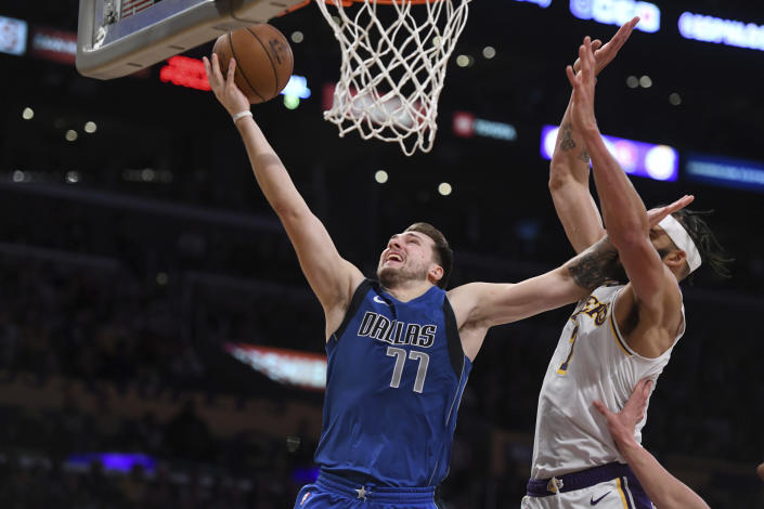 Dallas Mavericks guard Luka Doncic shoots a layup past Los Angeles Lakers center JaVale McGee during the second half of an NBA basketball game Sunday, Dec. 29, 2019, in Los Angeles. The Lakers won 108-95. (AP Photo/Michael Owen Baker)