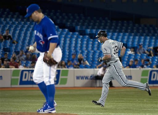 Chicago White Sox's Adam Dunn, right, rounds the bases after hitting a three-run home run as Toronto Blue Jays pitcher Brad Lincoln, left, looks down during the seventh inning of a baseball game in Toronto on Wednesday, Aug. 15, 2012. (AP Photo/The Canadian Press, Nathan Denette)