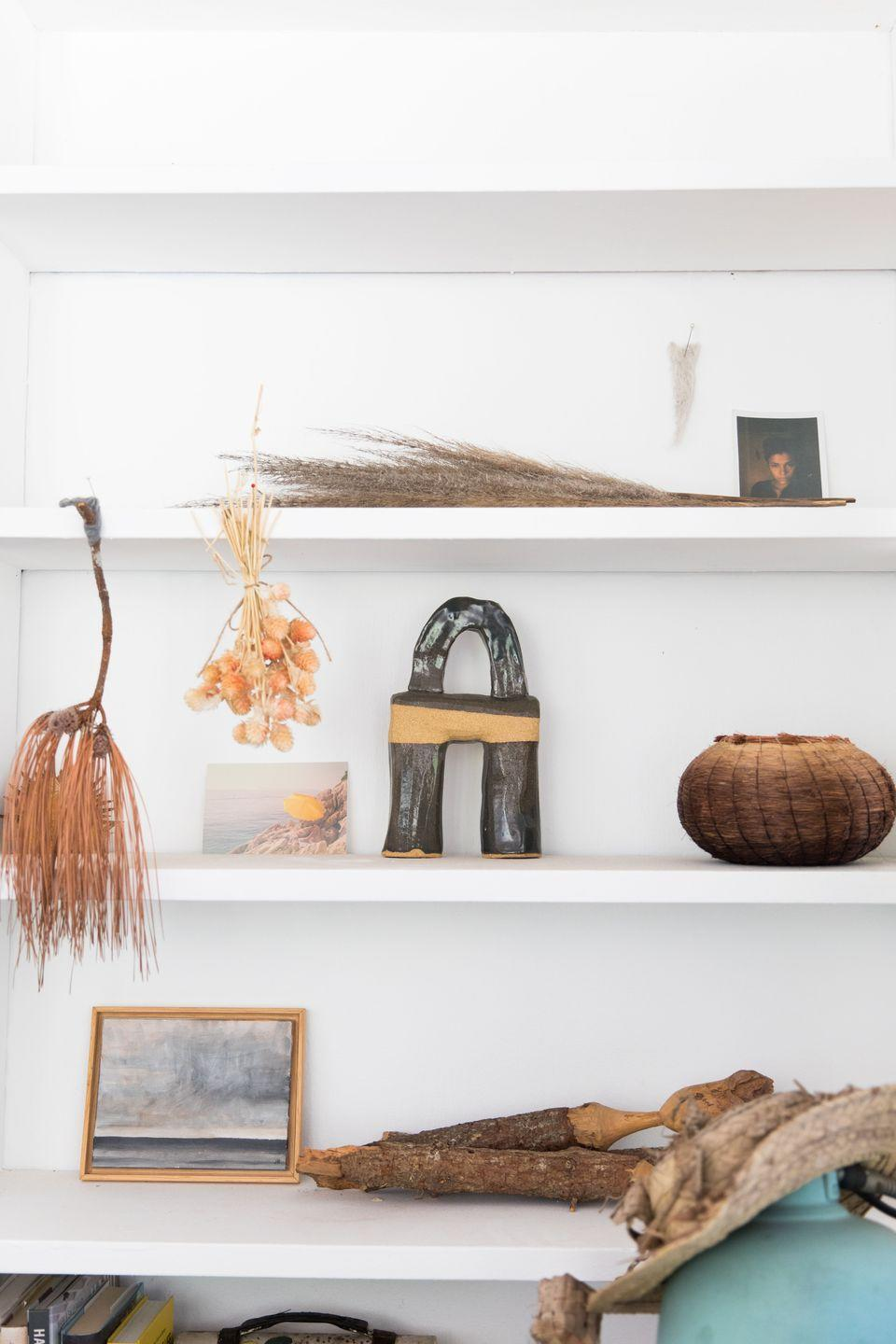"""<p>""""Some of my studio details... I am a collector of earthly objects with subtle tones and wild structures, I like to showcase them on the shelves around me as I work. I'm obsessed with nature's ability to showcase organised chaos, subtle colours and shading. The painting is by John Rapp, the sculpture by <a href=""""https://urldefense.com/v3/__https://www.beautifulnomad.com__;!!Ivohdkk!zWCIBW6SGBfMP6Z_LK_rXjTrXML7Pm1ZrMoo8qQILMpX4GfmM9xXWUT_Nji-Cx6BC_pJ8S55-J95AQ$"""" rel=""""nofollow noopener"""" target=""""_blank"""" data-ylk=""""slk:Beautiful Nomad"""" class=""""link rapid-noclick-resp"""">Beautiful Nomad</a> , and the basket by <a href=""""https://urldefense.com/v3/__http://adcockstudios.com__;!!Ivohdkk!zWCIBW6SGBfMP6Z_LK_rXjTrXML7Pm1ZrMoo8qQILMpX4GfmM9xXWUT_Nji-Cx6BC_pJ8S6jYMiAFQ$"""" rel=""""nofollow noopener"""" target=""""_blank"""" data-ylk=""""slk:Christine Adcock"""" class=""""link rapid-noclick-resp"""">Christine Adcock</a>. I carved the wooden faced sculptures myself.""""</p>"""