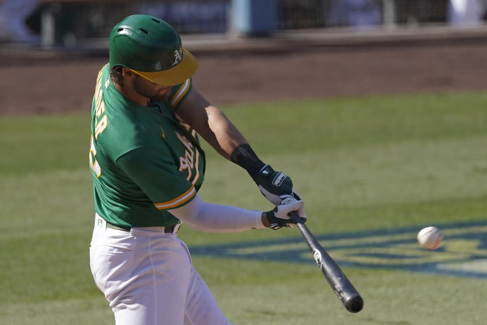 Oakland Athletics' Chad Pinder hits a solo home run against the Houston Astros during the fourth inning of Game 2 of a baseball American League Division Series in Los Angeles, Tuesday, Oct. 6, 2020. (AP Photo/Ashley Landis)