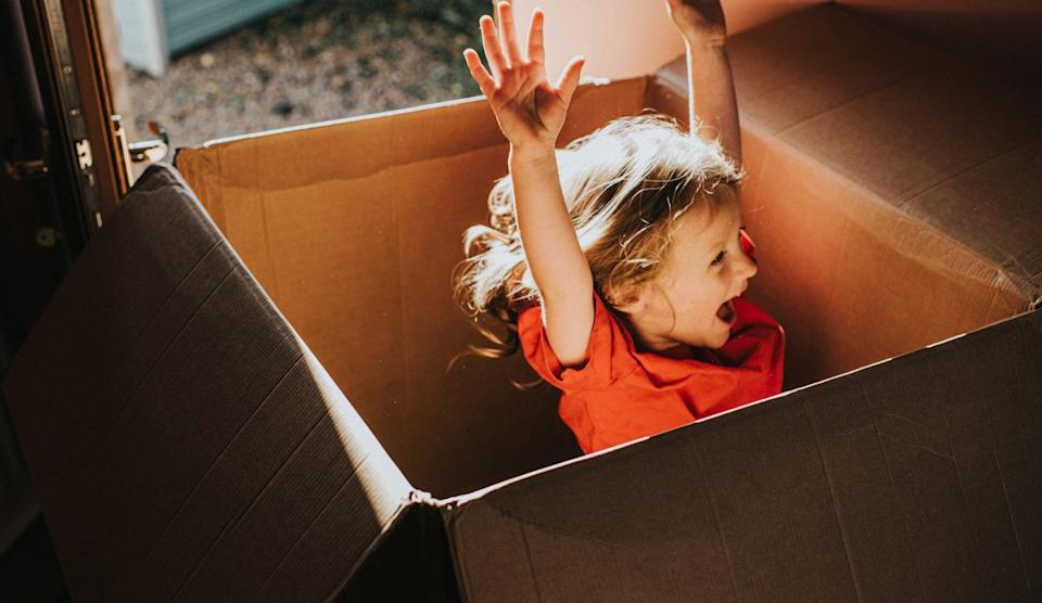 An image of a girl playing in a cardboard box.