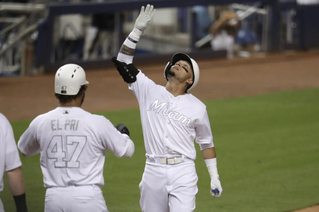 Miami Marlins' Isan Diaz, right, looks up after hitting a three-run home run during the third inning of a baseball game against the Philadelphia Phillies, Friday, Aug. 23, 2019, in Miami. (AP Photo/Lynne Sladky)