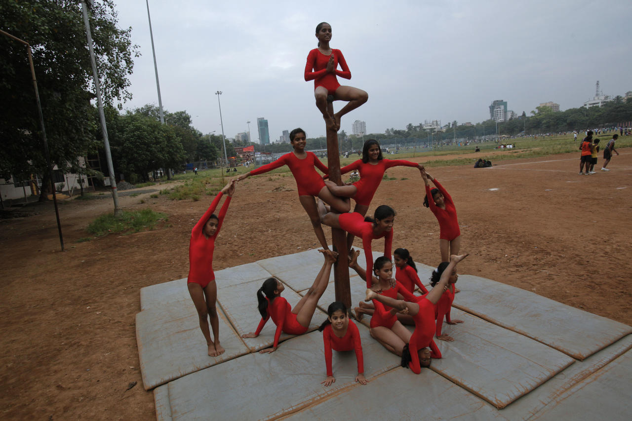 "Girls practise a Mallakhamb ""pyramid"" pose in the shape of a crown while suspended at the Shree Samartha Vyayam Mandir in Mumbai, October 19, 2012. Mallakhamb is an ancient Indian sport which originated as a complementary exercise for wrestling, but is now practiced as a sport in itself. The name is a combination of the words ""malla"", which means athlete or strong man, and ""khamba"", which means pole. Athletes perform a variety of yogic and gymnastic poses while suspended from a rope or on a pole. Practitioners say that the sport not only develops a healthy and strong body, but also strengthens willpower and helps compose the mind.      REUTERS/Vivek Prakash (INDIA - Tags: SPORT SOCIETY)"
