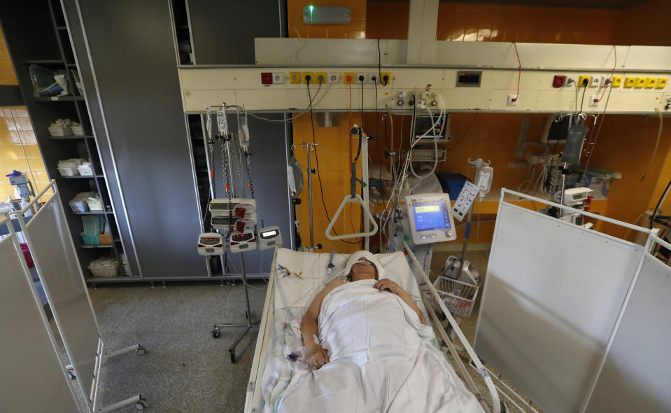 FILE - In this Oct. 1, 2020 file photo a COVID-19 patient lies on a bed in an intensive care unit (ICU) at Na Bulovce hospital in Prague, Czech Republic. Czechs had been assured it wouldn't happen again. But amid a record surge of coronavirus infections that's threatening the entire health system with collapse, the Czech Republic is adopting on Thursday exactly the same massive restrictions it slapped on citizens in the spring. Prime Minister Andrej Babis had repeatedly said these measures would never be repeated. (AP Photo/Petr David Josek, File)