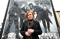 Julieann Campbell, the niece of Bloody Sunday victim Jackie Duddy, poses for a photograph by a mural depicting the late Bishop Edward Daly waving a white handkerchief as Jackie Duddy is carried away during the 1972 Bloody Sunday killings
