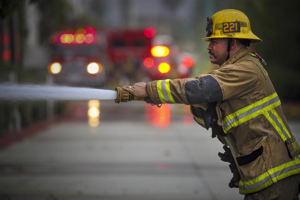 REDLANDS, CA - JUNE 05: San Bernardino County firefighter Javier Marquez uses a water hose to douse a massive warehouse fire on 2200 block of West Lugonia Avenue in Redlands. 2200 block of West Lugonia Avenue on Friday, June 5, 2020 in Redlands, CA. (Irfan Khan / Los Angeles Times via Getty Images)