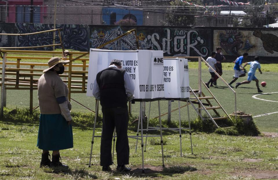 A couple votes in a non-binding referendum on whether Mexican ex-presidents should be tried for any illegal acts during their time in office, in San Miguel Topilejo, Mexico City, Sunday, August 1, 2021. (AP Photo/Christian Palma)