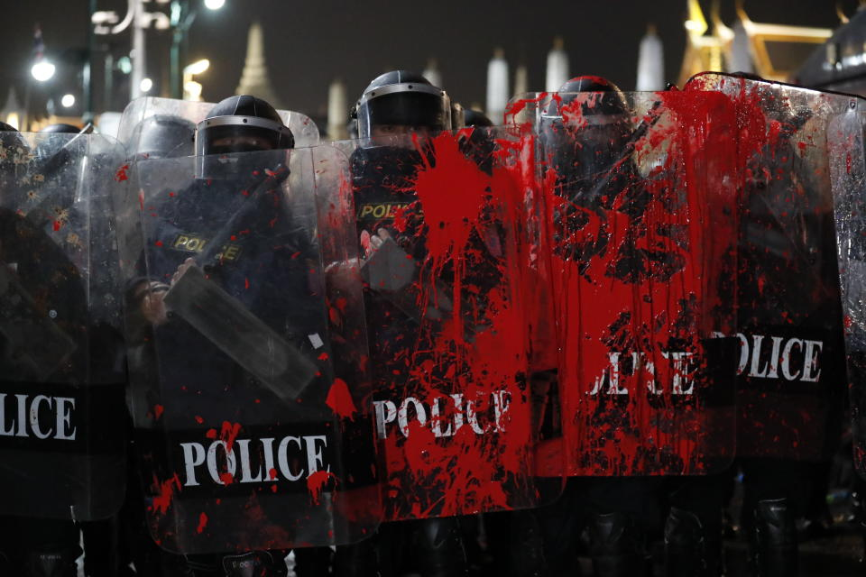 Red paint thrown by pro-democracy protesters is splattered on the shields of riot police standing guard outside the Grand Palace in Bangkok, Thailand, Saturday, Feb. 13,2021. The rally in the Thai capital was organized by the Ratsadorn movement, which campaigned last year for Prime Minister Prayuth Chan-ocha and his government to step down, the constitution to be amended and the reform of the monarchy to make it more accountable.(AP Photo/Sakchai Lalit)