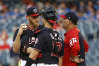 Washington Nationals starting pitcher Stephen Strasburg, left, speaks on the mound with catcher Yan Gomes and pitching coach Paul Menhart in the first inning of an interleague baseball game against the Chicago White Sox, Tuesday, June 4, 2019, in Washington. Chicago scored four runs against Strasburg in the first. (AP Photo/Patrick Semansky)