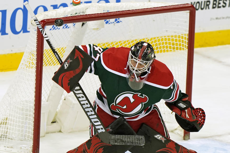 New Jersey Devils goaltender Aaron Dell deflects the puck during the second period of the team's NHL hockey game against the New York Islanders, Tuesday, March 2, 2021, in Newark, N.J. (AP Photo/Kathy Willens)