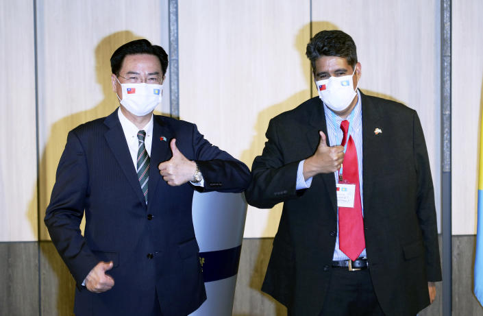 Palau President Surangel Whipps, right, is greeted by Taiwanese Foreign Minister Joseph Wu at a news conference in Taipei, Taiwan, Monday, March 29, 2021. Whipps arrived in Taiwan on Sunday for a five-day visit to kick-off a Taiwan-Palau travel bubble that starts April 1. (AP Photo/Chiang Ying-ying)