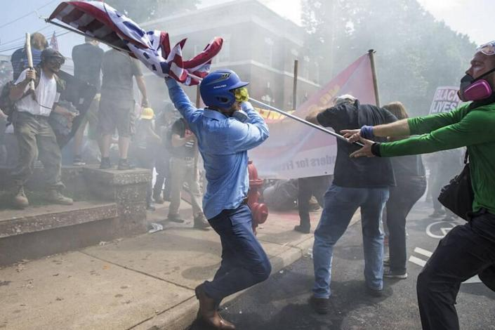 In 2017, a white supremacist tries to strike a counter protester with a white nationalist flag during clashes at Emancipation Park in Charlottesville, Virginia.