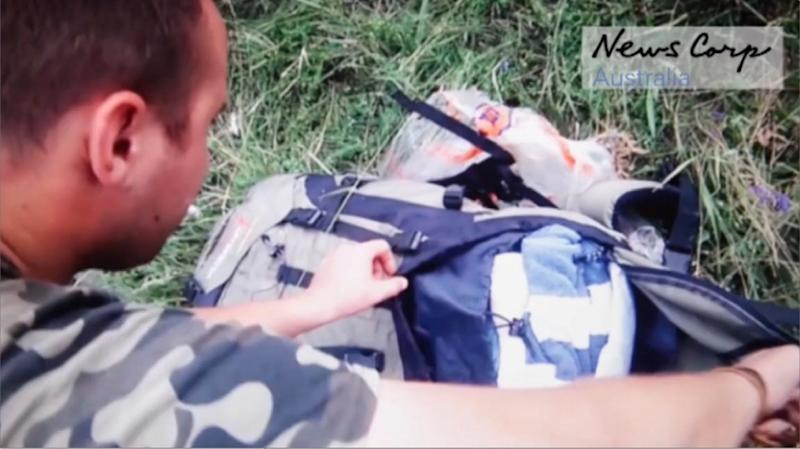This screen grab image taken from handout video released by News Corp Australia allegedly shows a Russian-backed rebel looking through personal belongs of passengers at the site of downed Malaysia Airlines flight MH17 on July 17, 2014 (AFP Photo/)