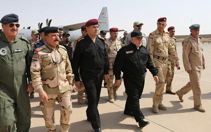 A handout picture released by the Iraqi prime minister's press office on July 9, 2017, shows Iraqi Prime Minister Haider al-Abadi (3rd from R) walking alongside police and army officers upon his arrival in Mosul (AFP Photo/HO)