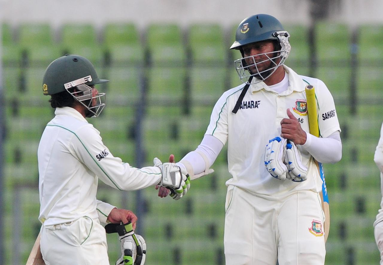 Bangladesh batsman Shakib Al Hasan (R) shakes hands with teammate Mominul Haque at close of play on the fourth day of the second Test match between Bangladesh and New Zealand at the Sher-e Bangla National Stadium in Dhaka on October 24, 2013. AFP PHOTO/ Munir uz ZAMAN        (Photo credit should read MUNIR UZ ZAMAN/AFP/Getty Images)
