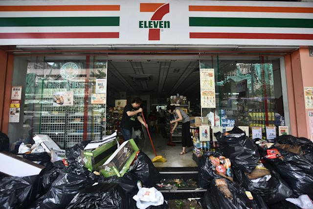 <p>Workers clear water and damaged goods from a convenience store in Macau on Aug. 24, 2017. (Photo: Anthony Wallace/AFP/Getty Images) </p>
