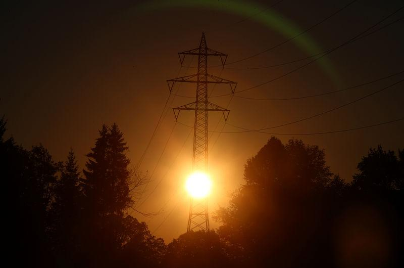 The sun rises behind high-voltage power lines and electricity pylons in Wall