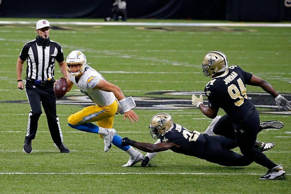Los Angeles Chargers quarterback Justin Herbert scrambles under pressure from Los Angeles Chargers running back Joshua Kelley and defensive end Cameron Jordan (94) in the first half of an NFL football game in New Orleans, Monday, Oct. 12, 2020.