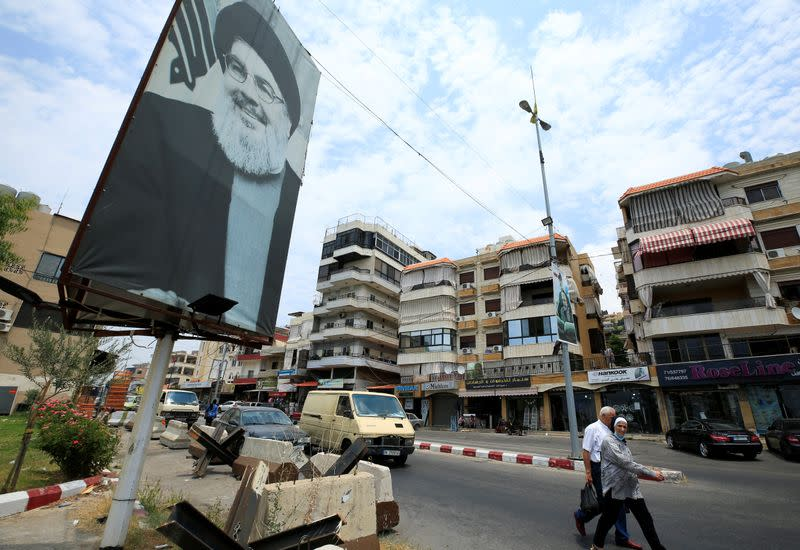 People walk past a poster depicting Lebanon's Hezbollah leader Sayyed Hassan Nasrallah, near Sidon