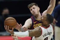 Portland Trail Blazers' Damian Lillard (0) drives to the basket against Cleveland Cavaliers' Isaiah Hartenstein during the second half of an NBA basketball game Wednesday, May 5, 2021, in Cleveland. (AP Photo/Tony Dejak)