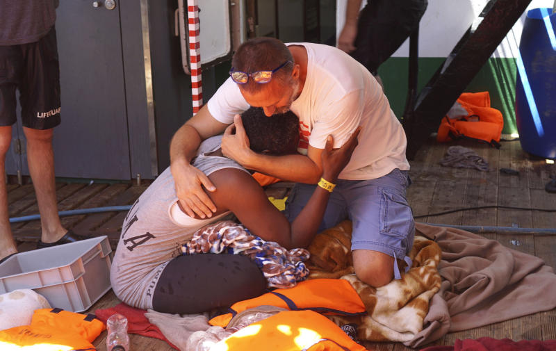 A migrant is comforted by a crew member of the Open Arms Spanish humanitarian boat off the coast of the Sicilian island of Lampedusa, southern Italy, Sunday, Aug.18, 2019. An Open Arms spokeswoman tells The Associated Press that the humanitarian group is not willing to sail to Spain's southernmost Algeciras port given the emergency situation that they are experiencing inside the boat. (AP Photo/Francisco Gentico)