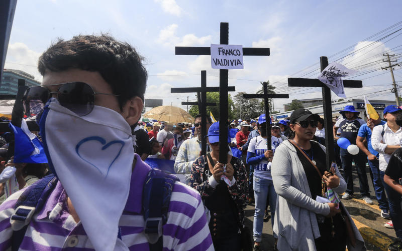 Anti-government protesters join a Stations of the Cross procession on Good Friday, carrying signs demanding the release of political prisoners in Managua, Nicaragua, Friday, April 19, 2019. Good Friday religious processions in Nicaragua's capital have taken a decidedly political tone as people have seized on a rare opportunity to renew protests against the government of President Daniel Ortega. (AP Photo/Alfredo Zuniga)