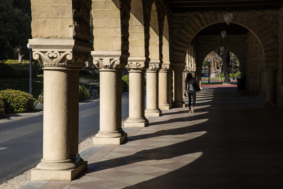 STANFORD, CA - MARCH 09: A person walks past archways during a quiet morning at Stanford University on March 9, 2020 in Stanford, California. Stanford University announced that classes will be held online for the remainder of the winter quarter after a staff member working in a clinic tested positive for the Coronavirus. (Photo by Philip Pacheco/Getty Images)