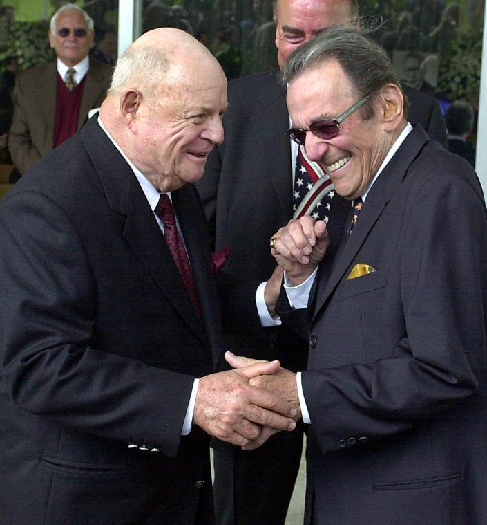FILE - In this April 1, 2002, file photo, comedians Don Rickles, left, and Norm Crosby arrive for a ceremony honoring comedian Milton Berle at Hillside Memorial Park and Mortuary in Los Angeles. Crosby, the deadpan mangler of the English language who thrived in the 1960s, '70s and '80s as a television, nightclub and casino comedian, has died. He was 93. Crosby's daughter-in-law, Maggie Crosby, told the New York Times that the comic died Saturday, Nov. 7, 2020 of heart failure in Los Angeles. (AP Photo/Nick Ut, File)