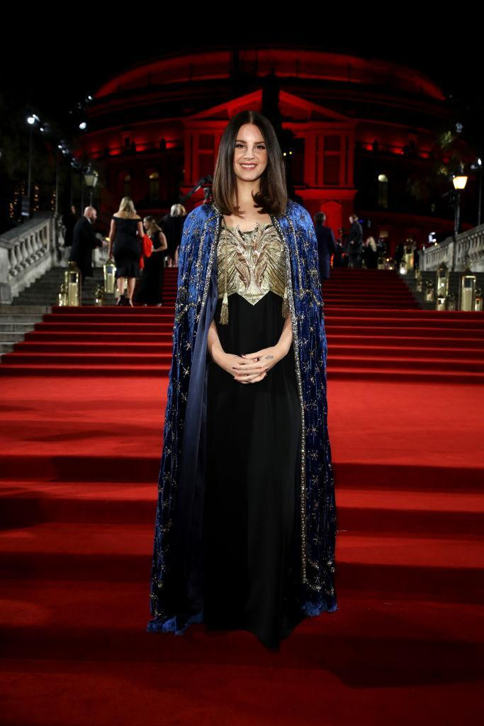 <p>Lana del Rey wore a midnight blue embroidered cloak over her metallic ensemble on the red carpet this year.<em> [Photo: Getty]</em> </p>
