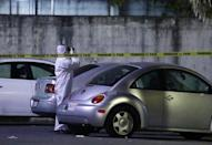 A forensic technician takes pictures at a crime scene, where men were killed inside a home by unknown assailants, in the municipality of San Nicolas de los Garza, Mexico, January 27, 2018. Picture taken January 27, 2018. REUTERS/Jorge Lopez