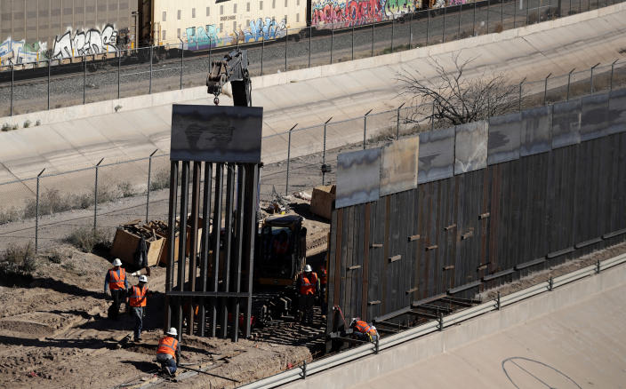 FILE - In this Jan. 22, 2019, file photo, workers place sections of metal wall as a new barrier is built along the Texas-Mexico border near downtown El Paso. The government is working on replacing and adding fencing in various locations, and Trump in February declared a national emergency to get more funding for the wall. (AP Photo/Eric Gay, File)