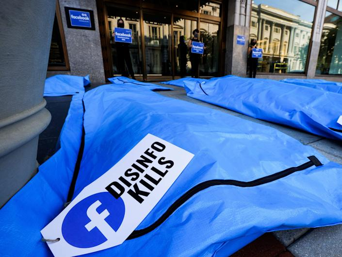 """a blue body bag in the foreground with a tag including the facebook logo and the words """"disinfo kills"""""""