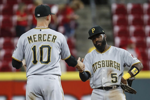 Pittsburgh Pirates second baseman Josh Harrison (5) and shortstop Jordy Mercer (10) celebrate after the team's 5-4 win in 12 innings in a baseball game against the Cincinnati Reds, Wednesday, May 23, 2018, in Cincinnati. (AP Photo/John Minchillo)