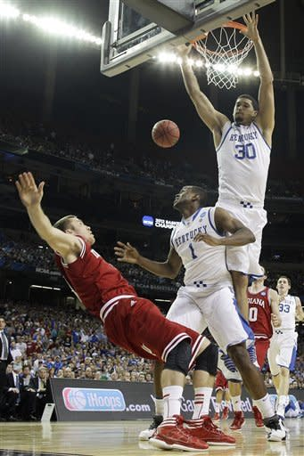 Indiana's Jordan Hulls falls as Kentucky's Darius Miller (1) and Kentucky's Eloy Vargas defend during the first half of an NCAA tournament South Regional semifinal college basketball game Friday, March 23, 2012, in Atlanta. (AP Photo/John Bazemore)