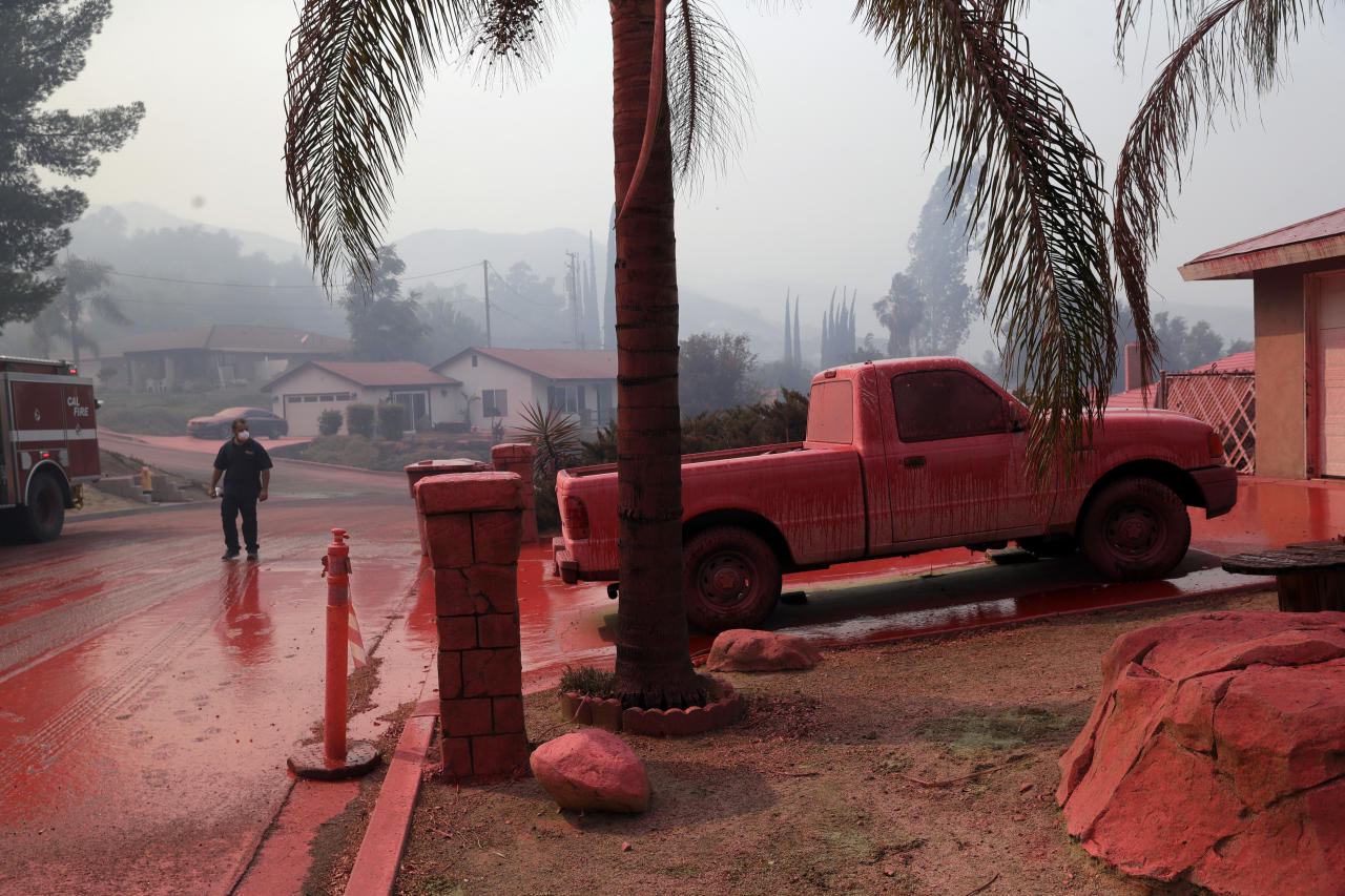 A truck and a street are covered in fire retardant dropped by an air tanker as crews battle a wildfire Friday Aug. 10 2018 in Lake Elsinore Calif