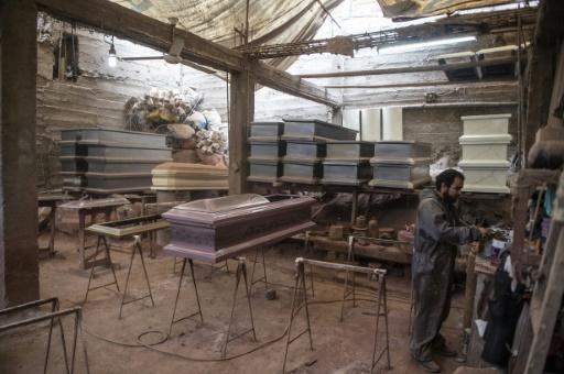 A worker prepares to paint a coffin at a factory in Lima's Juan de Lurigancho district