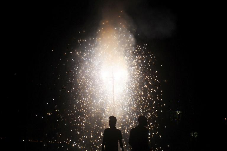 Revellers watch fireworks at a park during Diwali, the festival of lights, in Kolkata on November 13, 2012. The festival marks the victory of good over evil and commemorates the time when Hindu God Lord Rama achieved victory over Ravana and returned to his kingdom Ayodhya after 14 years in exile. AFP PHOTO/Dibyangshu SARKAR