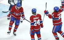 Montreal Canadiens' Artturi Lehkonen, left, celebrates his goal with teammates Phillip Danault and Ben Chiarot during the second period of an NHL Stanley Cup playoff hockey game in Montreal, Sunday, June 6, 2021. (Paul Chiasson/The Canadian Press via AP)
