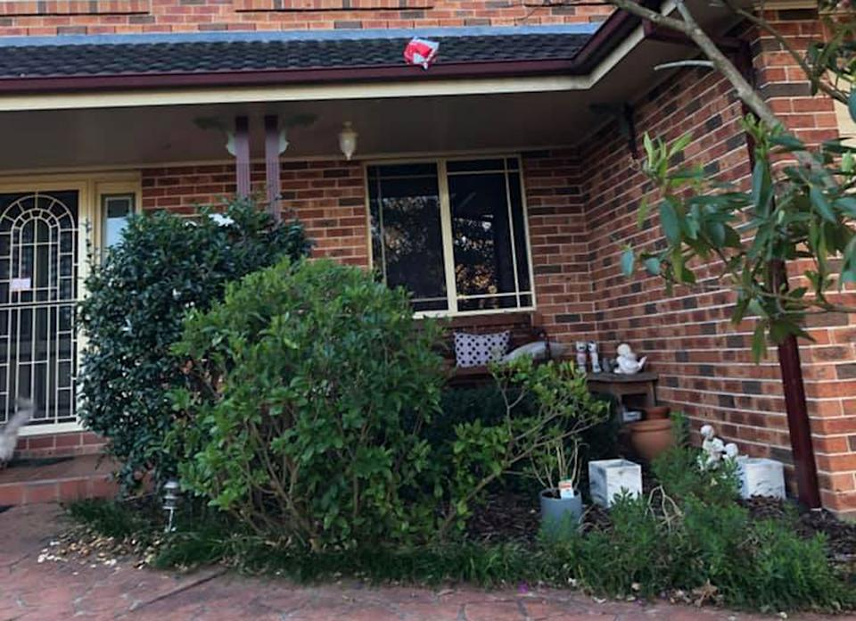Pictured is an Australia Post parcel in a roof gutter. A Castle Hill woman claims Australia Post delivered her parcel to her by throwing it on her roof.