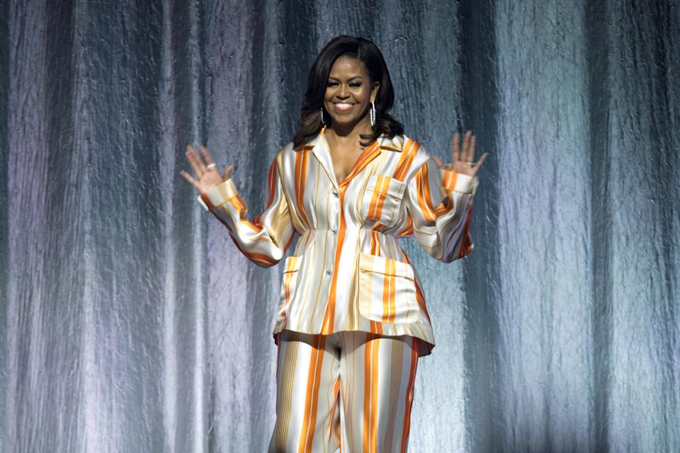 """Former first lady Michelle Obama waves on stage at the AccorHotels Arena during a book tour to promote her memoir """"Becoming"""" in Paris, France, April 16, 2019.  REUTERS/Charles Platiau"""
