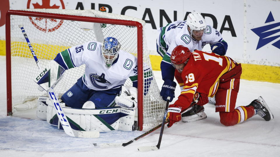 Vancouver Canucks' Bo Horvat, top right, checks Calgary Flames' Matthew Tkachuk, center, as Canucks goalie Thatcher Demko looks on during second-period NHL hockey game action in Calgary, Alberta, Monday, Jan. 18, 2021. (Jeff McIntosh/The Canadian Press via AP)