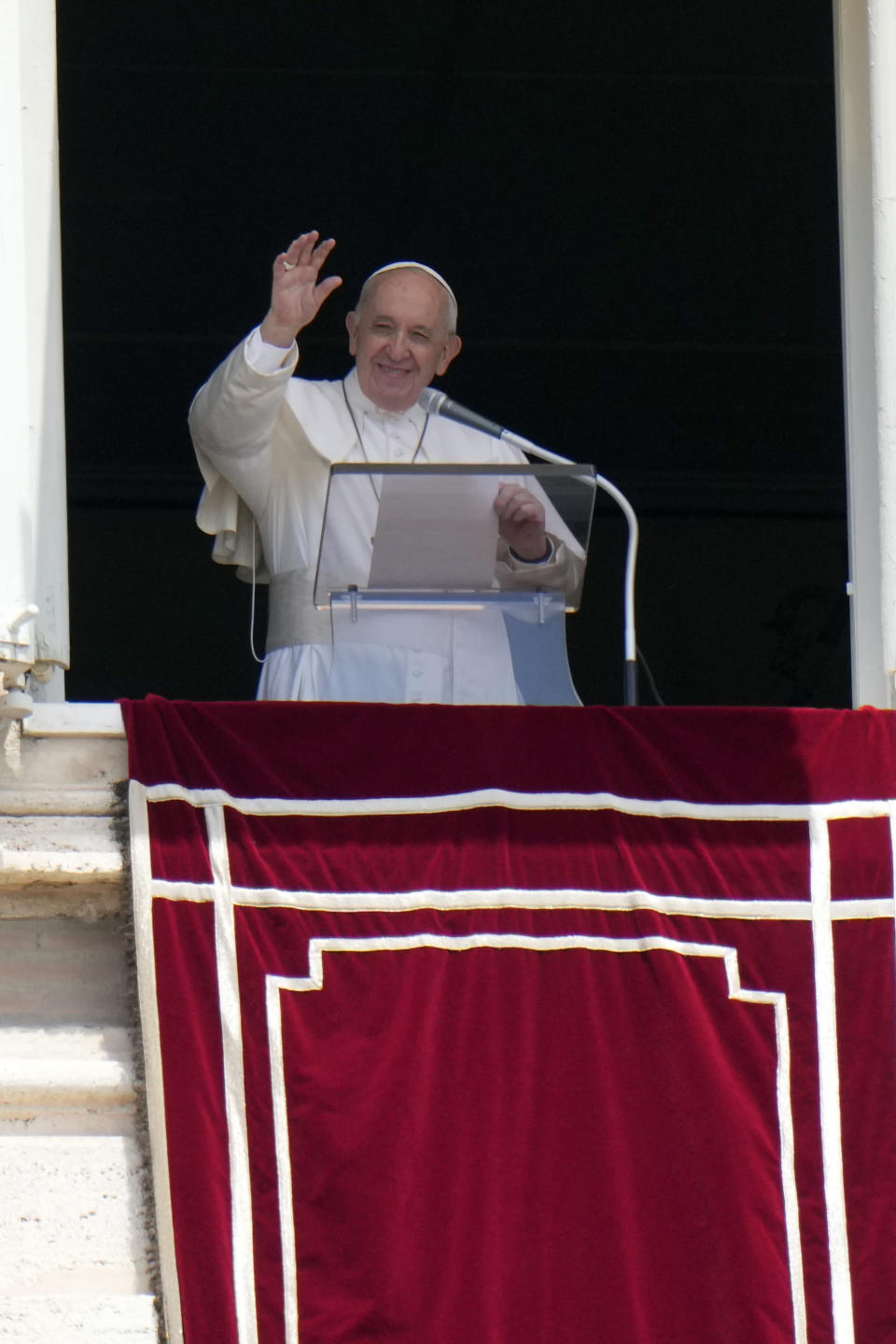 Pope Francis waves to faithful during the Angelus noon prayer from the window of his studio overlooking St.Peter's Square, at the Vatican, Sunday, July 4, 2021. In a brief announcement Sunday afternoon the Vatican said Pope Francis has gone to a Rome hospital for scheduled surgery for a stenosis, or restriction, of the large intestine. (AP Photo/Alessandra Tarantino)