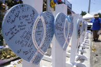 A wooden heart at a makeshift memorial remembers the family of Vishal and Bhavna Patel, who died along with their 1-year-old daughter Aishani, in the collapse of the nearby Champlain Towers South building, Wednesday, July 14, 2021, in Surfside, Fla. Removal and recovery work continues at the site of the partially collapsed condo building, Wednesday, in Surfside. (AP Photo/Lynne Sladky)