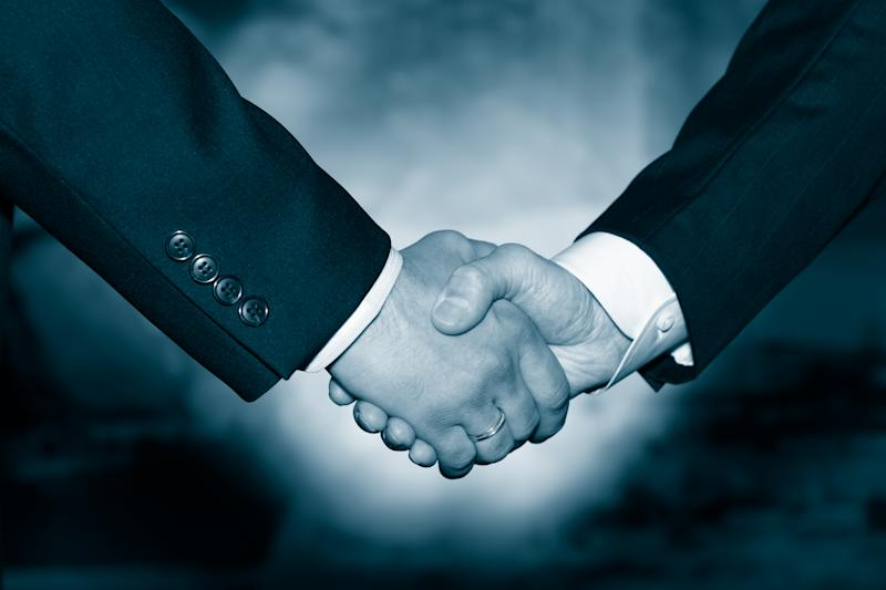 Two businessmen shaking hands, as if in agreement.