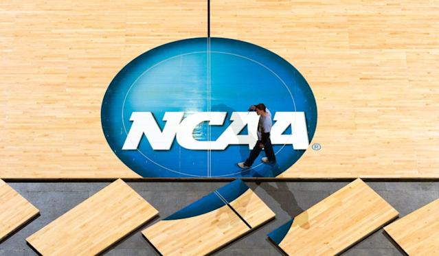 """Workers place the court on the floor at the CenturyLink Center in Omaha for the NCAA men's basketball tournament. <span class=""""copyright"""">(Matt Miller / Associated Press)</span>"""