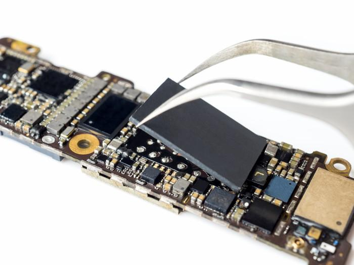 A smartphone logic board with a large chip being removed from it by a pair of pliers.