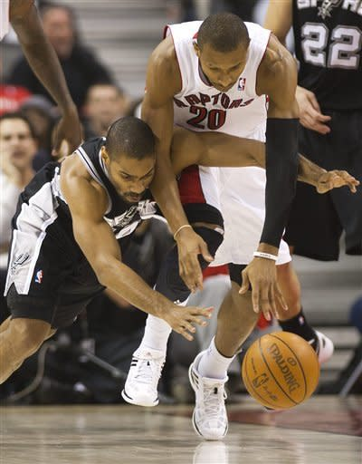 Toronto Raptors guard Leandro Barbosa, right, battles for the ball against San Antonio Spurs guard Gary Neal, left, during first-half NBA basketball game action in Toronto on Wednesday, Feb. 15, 2012. (AP Photo/The Canadian Press, Nathan Denette)