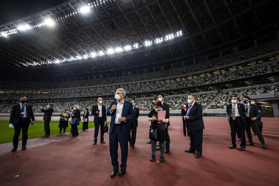 "IOC President Thomas Bach, center, visits the National Stadium, the main venue for the 2020 Olympic and Paralympic Games postponed until July 2021 due to the coronavirus pandemic, in Tokyo Tuesday, Nov. 17, 2020. Bach said during this week's trip to Tokyo that he is ""encouraging"" all Olympic ""participants"" and fans to be vaccinated - if one becomes available - if they are going to attend next year's Tokyo Olympics. (Behrouz Mehri/Pool Photo via AP)"