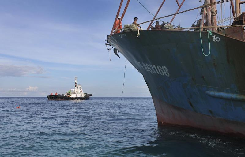 Photo released on April 19, 2013 shows the Chinese fishing boat (R) that ran aground off Tubbataha Reef being towed away by a tugboat (AFP Photo/Philippine Coast Guard)