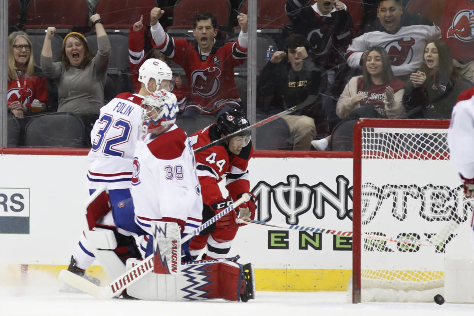New Jersey Devils fans react as Devils left wing Miles Wood (44) shoves the puck into the net behind Montreal Canadiens goaltender Charlie Lindgren (39) during the first period of an NHL hockey game Tuesday, Feb. 4, 2020, in Newark, N.J. (AP Photo/Kathy Willens)